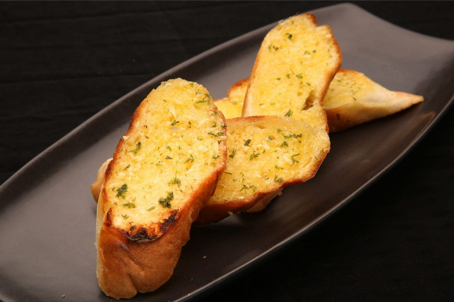 slices of weed garlic bread on a black abstract plate