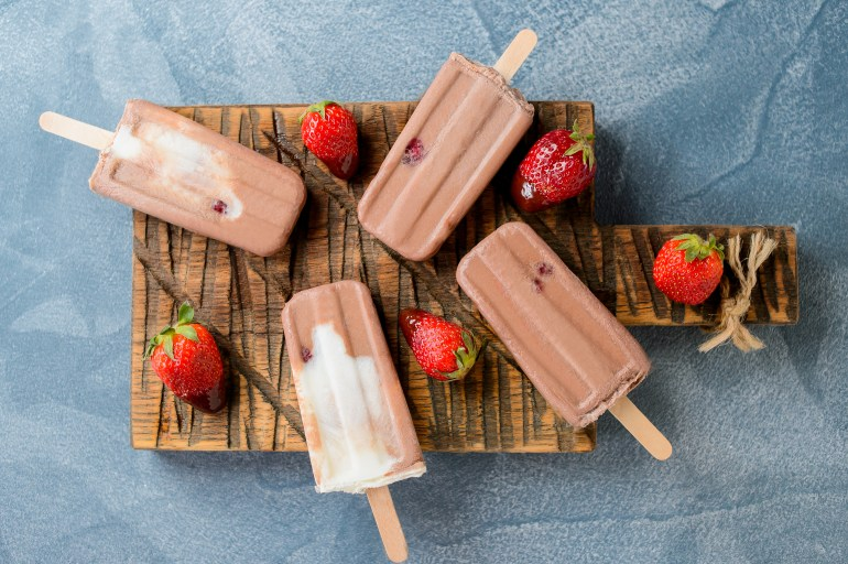 weed chocolate popsicles on a wooden cutting board with strawberries beside them