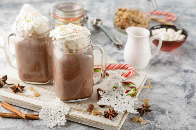 Two jars with weed hot chocolate in them on a wooden cutting board. Lots of cutlery and cups in the background. a weed edible drink recipe.