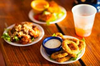 Three plates and a plastic cup with liquid in it. One of the plates as weed infused onion rings on it with dipping sauce