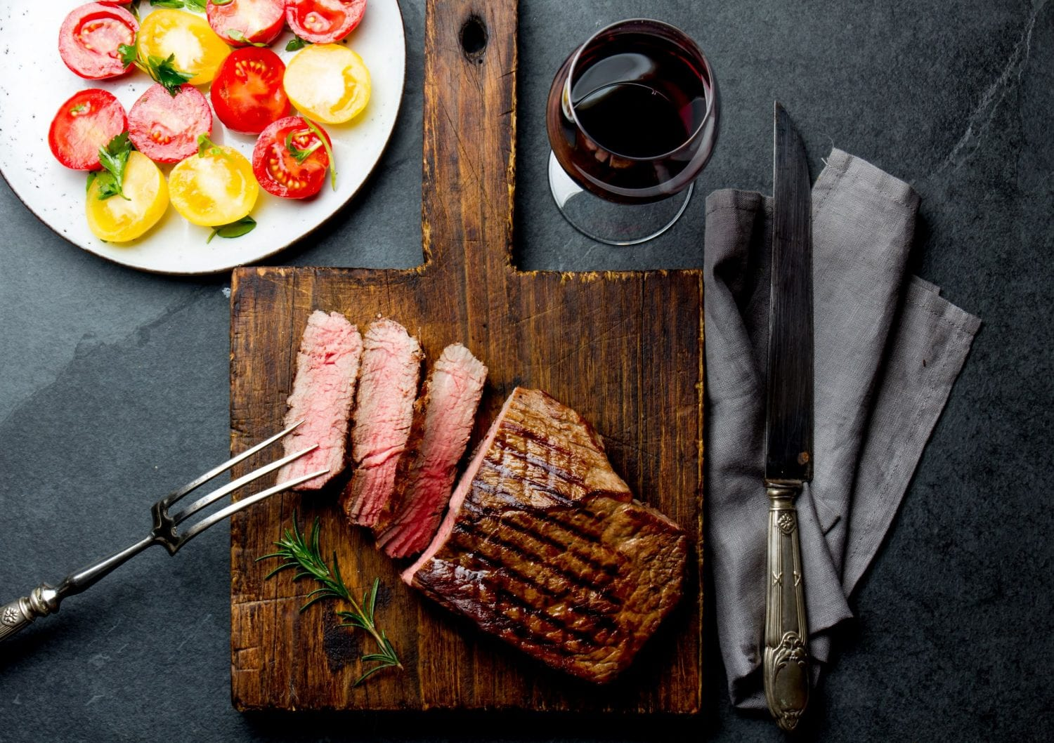 Weed steak with slices cut out of it on a cutting board with a knife and other cooking utensils beside it. There is a glass of wine and a plate of peppers in the background