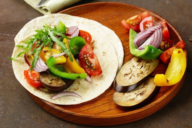 Cannabis infused fajitas With veggies besides them on a wooden plate