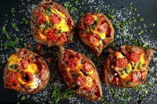 Overhead shot of five weed baked stuffed potatoes With lots of tomatoes and Parmesan cheese sprinkled over top of them