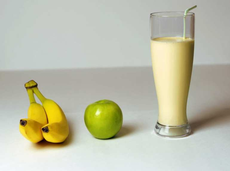 Cannabis infused banana smoothie on the white table with a green apple and two bananas beside it. a weed edible drink recipe.