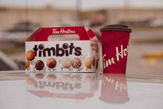 A cuppa coffee from Tim Hortons on the hood of a car with Tim bits from Tim Hortons beside it