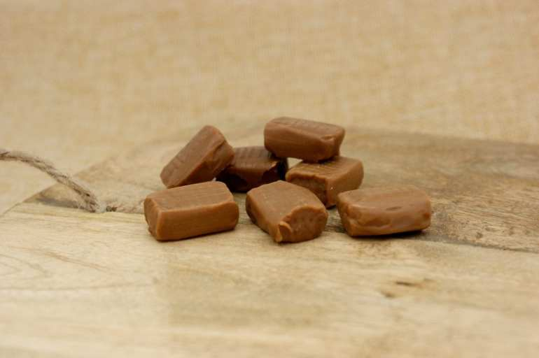 Infused caramel cubes on a brown wooden table shot in macro