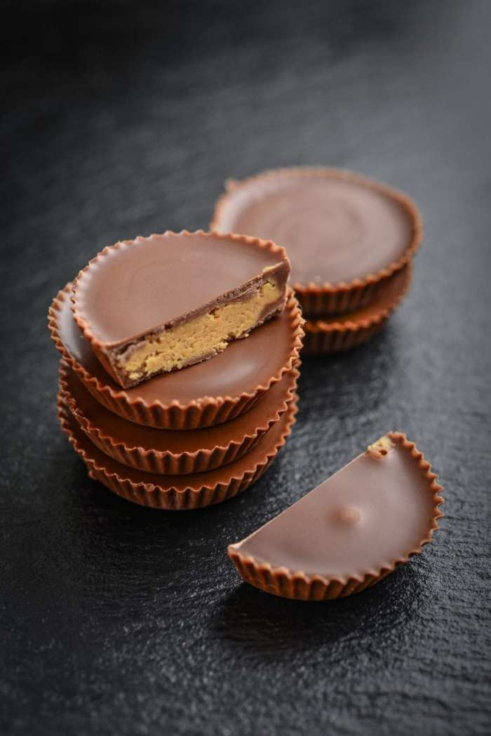 a stack of weed peanut butter cups on a black table with more peanut butter cups in the background