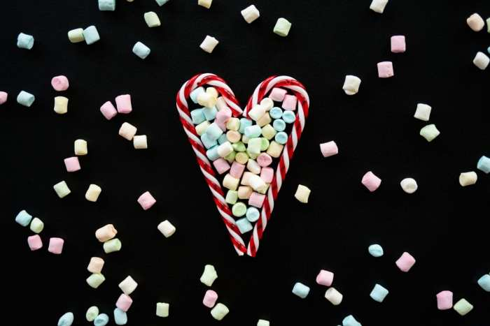 two candy canes making the shape of a heart with weed butter mints spread around them on the table