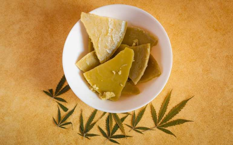 bowl with cannabis butter in it on a brown table with weed leaves spread around it on a table.