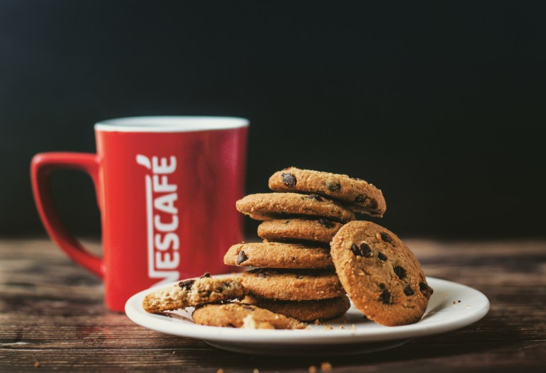 CBD chocolate chip cookies sitting on top of a white plate. A red coffee mug is behind them.