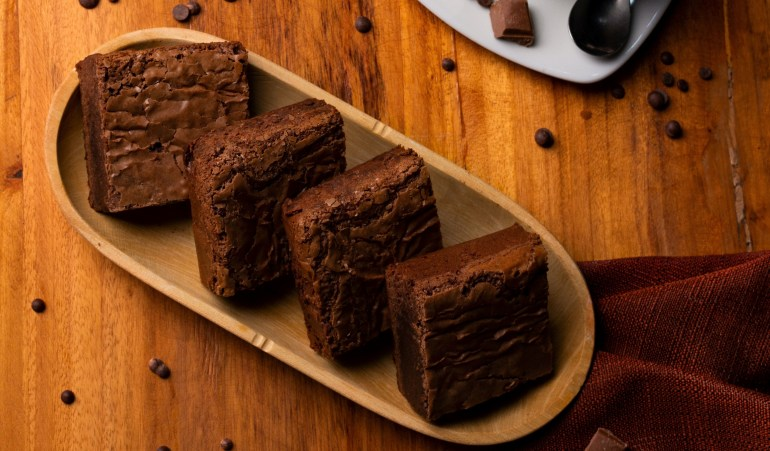 CBD brownies cut into four equal size pieces. The brownies sit on a wooden tray on a wooden table.