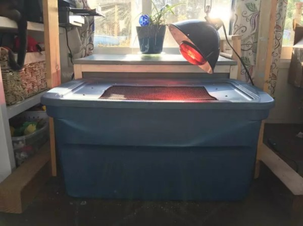 This is the set up with a heat lamp stand on either side. The lamp is clipped to a wire strung between the posts.