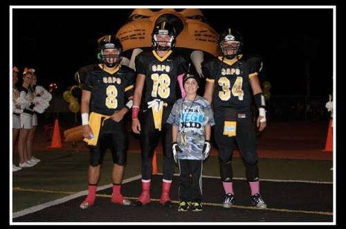 (From L to R) Capistrano Valley football captains Matthew Gordon, Cole Muusse, honorary captain Kurt Perryman and Philip O'Shea prepare walk to take part in the coin toss before a game against Dana Hills on October 18. Photo by Doug McDonough/Jonny Perryman