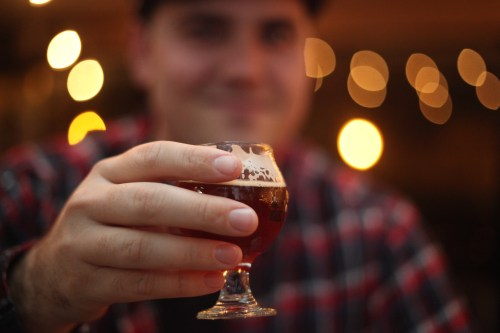 A patron of The BrewHouse in San Juan Capistrano salutes the camera with a taster-sized beer.