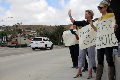 (From right to left) San Clemente residents Kelly Morris and Traci Arth-Streets wave to motorists passing by on the Camino De Estrella overpass during a Tuesday, May 21 protest against new abortion bans that several states have recently passed. Photo: Shawn Raymundo