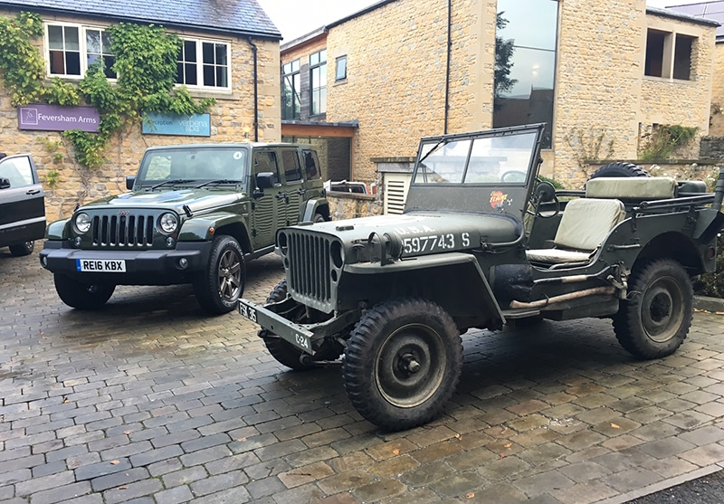 Willys Jeep alongside a current Jeep Wrangler