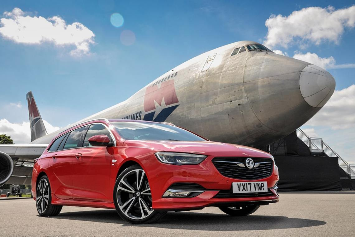 Vauxhall Insignia Sport Tourer on the road - with a plane