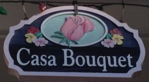 wooden sign with flowers and Casa Bouquet