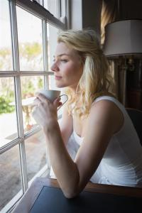 Woman at window with tea (Large)