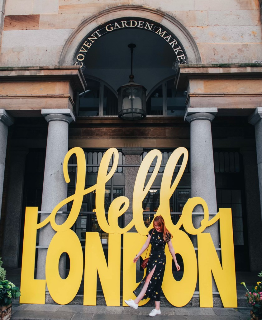 travel blogger stood infront of the hello London sign in Covent Market