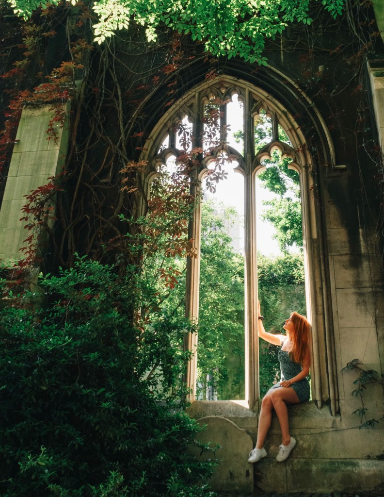 Travel blogger sat in an archway in the church ruins of St. Dunstan in the East