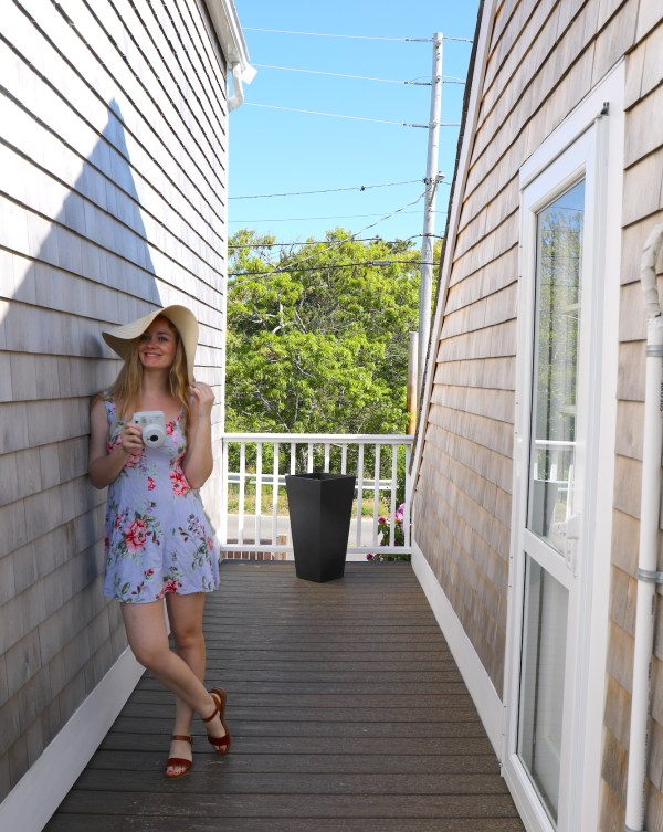 girl leaning on side of house