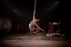 Image shows a frozen moment of action. Alana Bloom is hanging by a gripped hand from a vertical skein of silk above a dingy concrete floor. Her body arches backwards as she turns her head to the silk above her, legs bent at the knees, soles of feet facing the back of her head. In the shadows of the background, is a miniature theatre set with red curtains, with a stag's head resting on the floor in front of it
