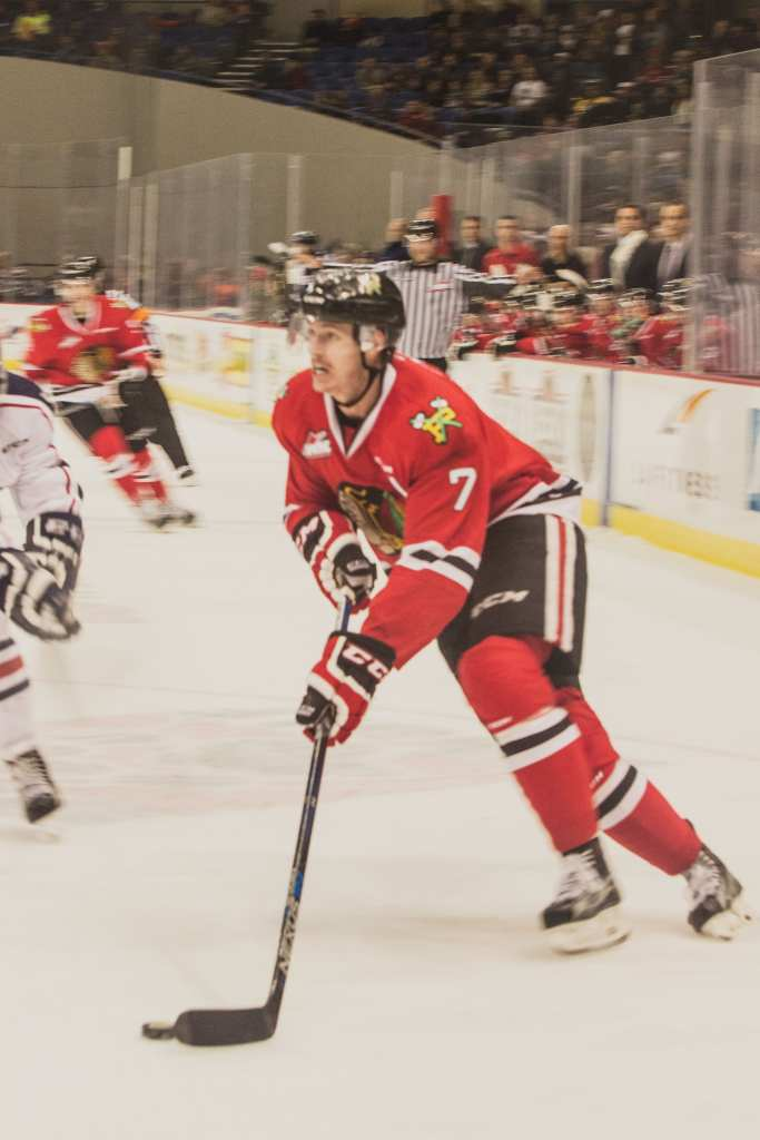 Paul Bittner looks up to plan his attack to goal. Cody Glass, for the Winterhawks, faces off against Nolan Yaremko, from Tri–City Americans. Bittner scored the fifth goal of the game.