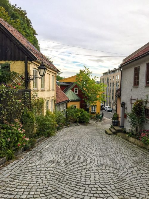 Travel in Norway on a Tight Budget Cobblestone street with colorful houses in Oslo Norway Europe