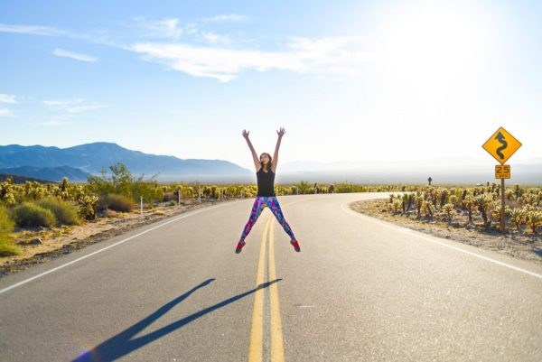 Meet Clumsy Traveler Rachel; girl jumping in the middle of the road Joshua Tree