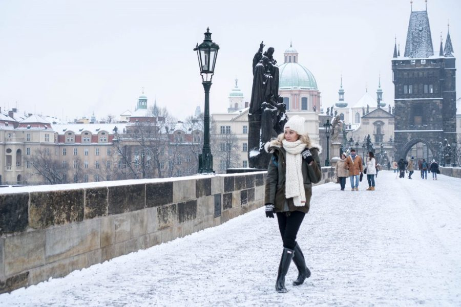 Winter Wonderland Lookbook; blonde girl on Charles Bridge Prague chunky knit scarf and beanie snow