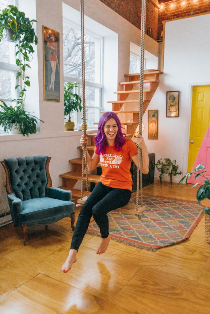 Staying at The Funky Loft in Brooklyn, New York; girl with purple hair on indoor swing in retro apartment