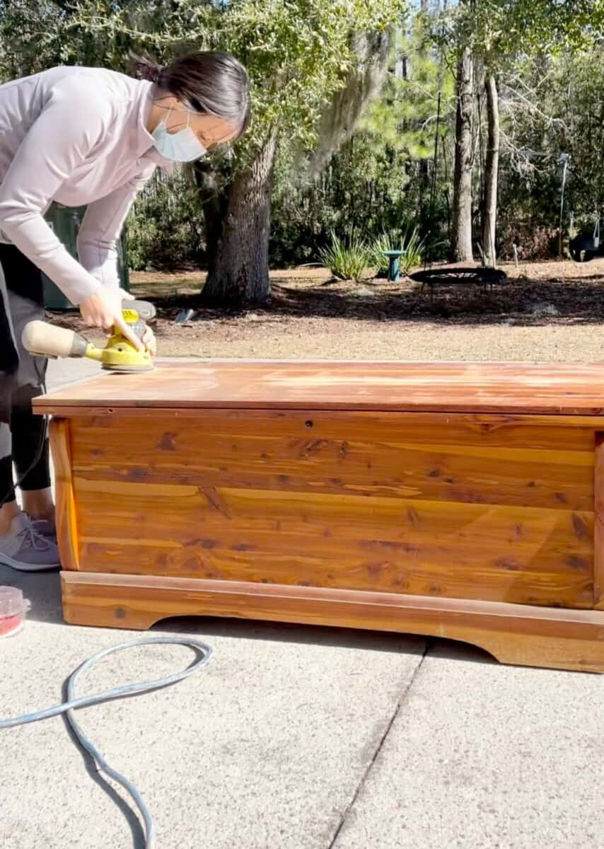 Sanding the rest of the varnish from the cedar hope chest.