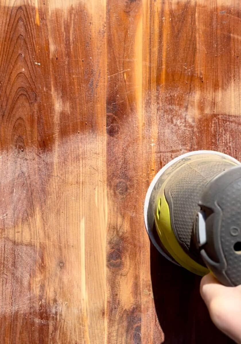 Removing varnish from cedar hope chest using orbital sander.