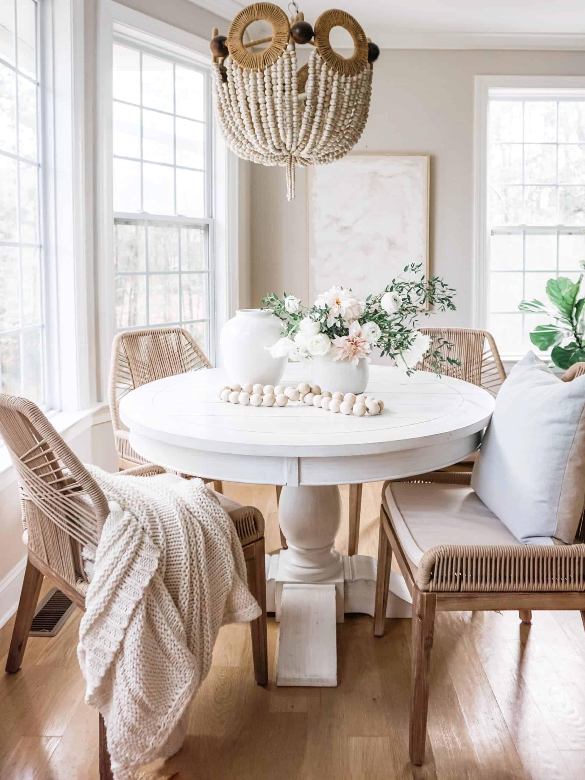 Coastal breakfast nook with round dining table and rope dining chairs.