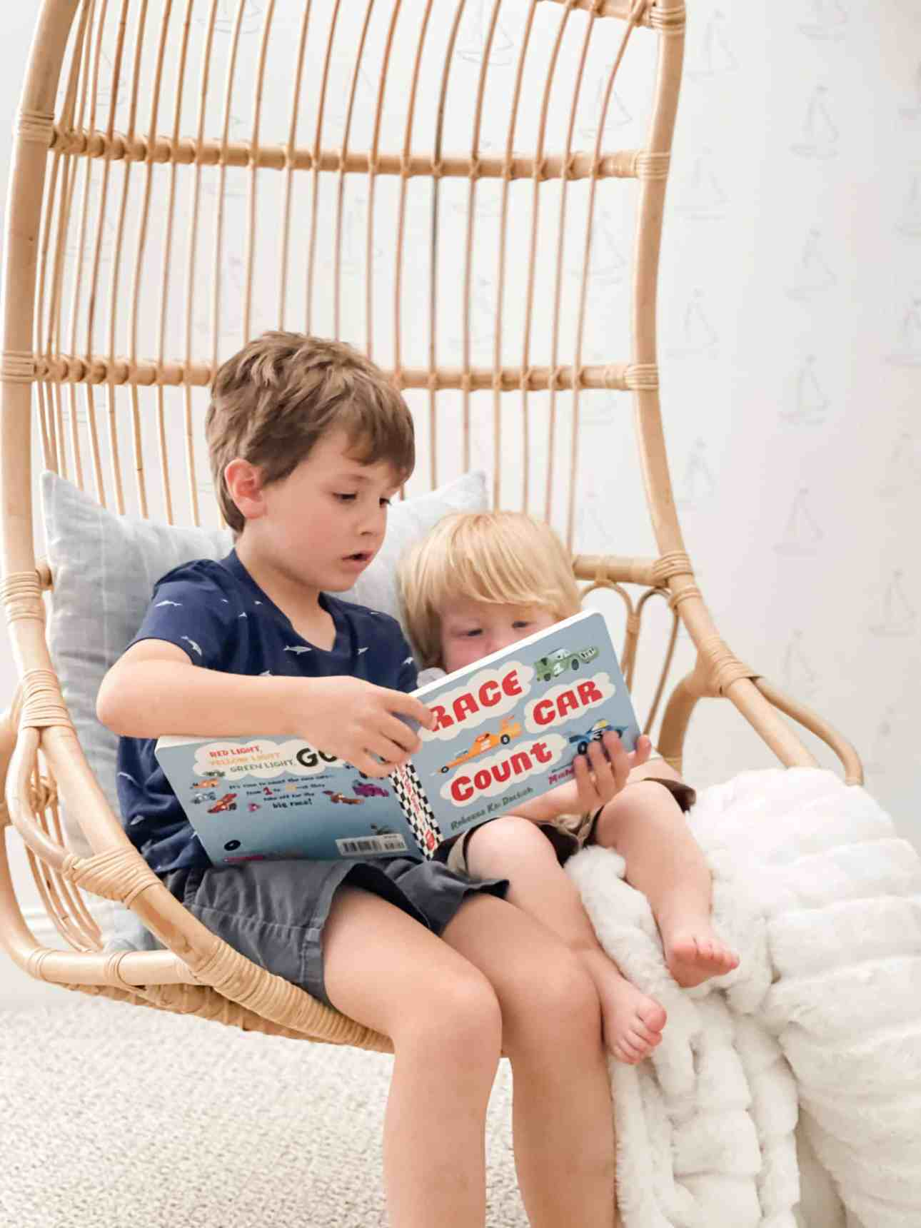 Older brother reading a book to little brother in the hanging rattan chair from Serena & Lily.
