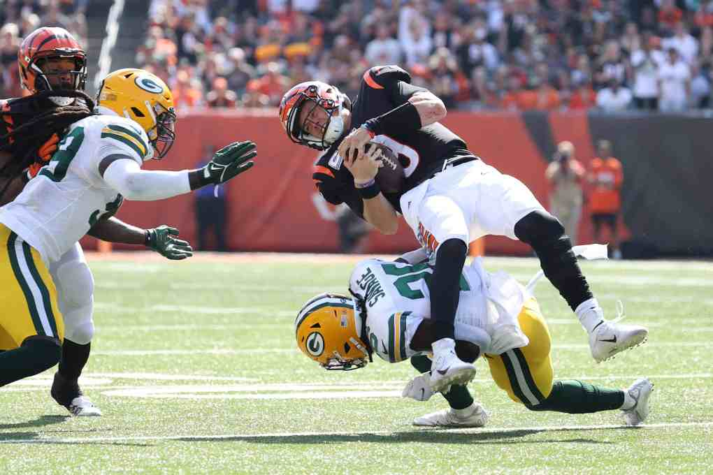 Joe Burrow #9 of the Cincinnati Bengals is hit by Darnell Savage #26 of the Green Bay Packers during the second quarter at Paul Brown Stadium on October 10, 2021 in Cincinnati, Ohio.