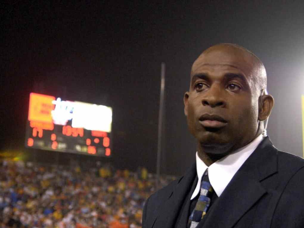 Television commentator Deon Sanders stands on the sidelines during the AFC-NFC Pro Football Hall of Fame Game against the Pittsburgh Steelers at Fawcett Stadium August 5, 2007 in Canton, Ohio.