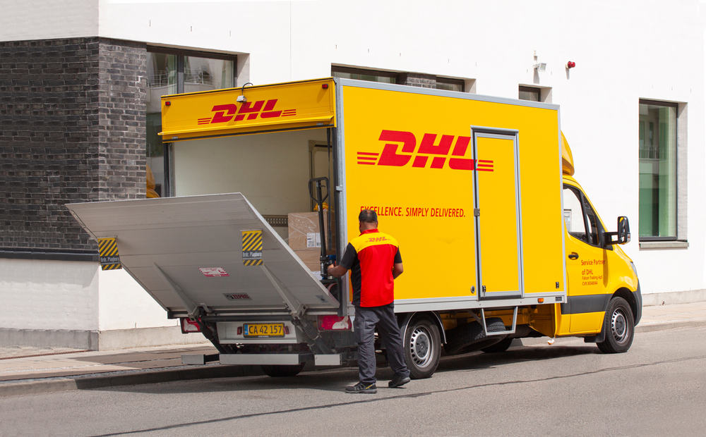 Delivery man in uniform opening tailgate loader on a DHL lorry