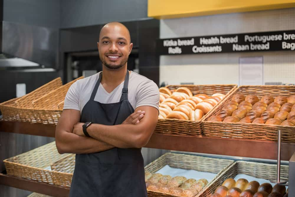Smiling baker man standing with fresh bread at bakery