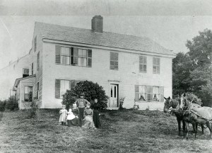 Colonial house with family and horses in front