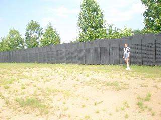 An uncountable number of FEMA coffins were discovered on a lonely road approximately 50 miles outside of Atlanta. The discovery was made by Sherrie Wilcox who has since bugged out for her own safety. The person in the photo is Sherrie Wilcox who is posing for a photo with the FEMA coffins she discovered outside of Atlanta, 4 years ago