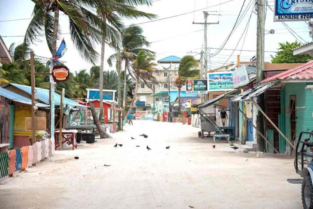 Top 10 Best Things To Do in Belize featured by top US travel blog, The Common Traveler: image of dirt street with colorful buildings in Caye Caulker, Belize