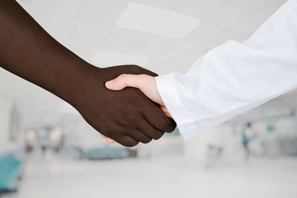 Nurse practitioner shaking hands with African American man to stand against racial health disparities