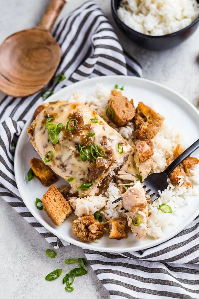 Chicken breast covered in cheese, on a white plate with white rice and croutons