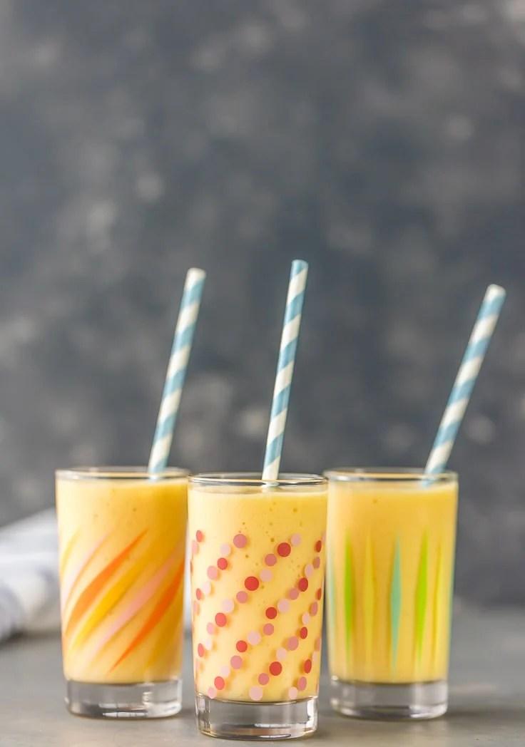 three simple mango smoothies with straws