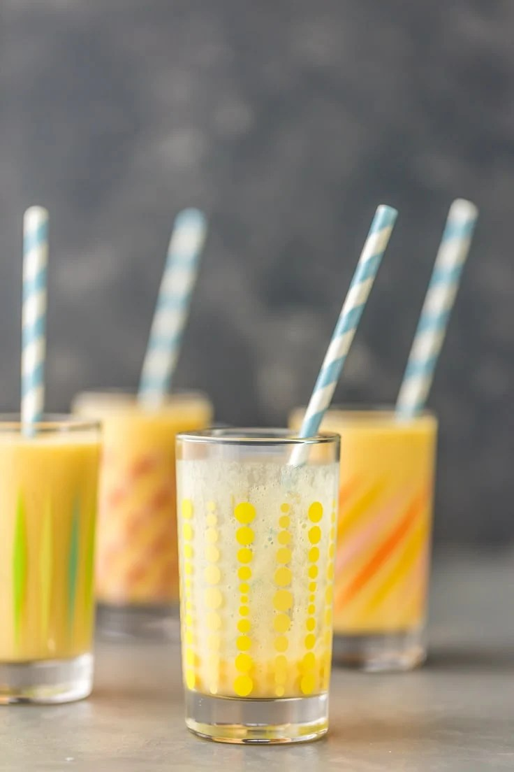 four glasses with simple mango smoothies