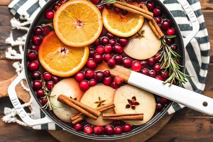 A pot of hot cranberry apple hot cider garnished with orange slices, cloves, and cinnamon sticks