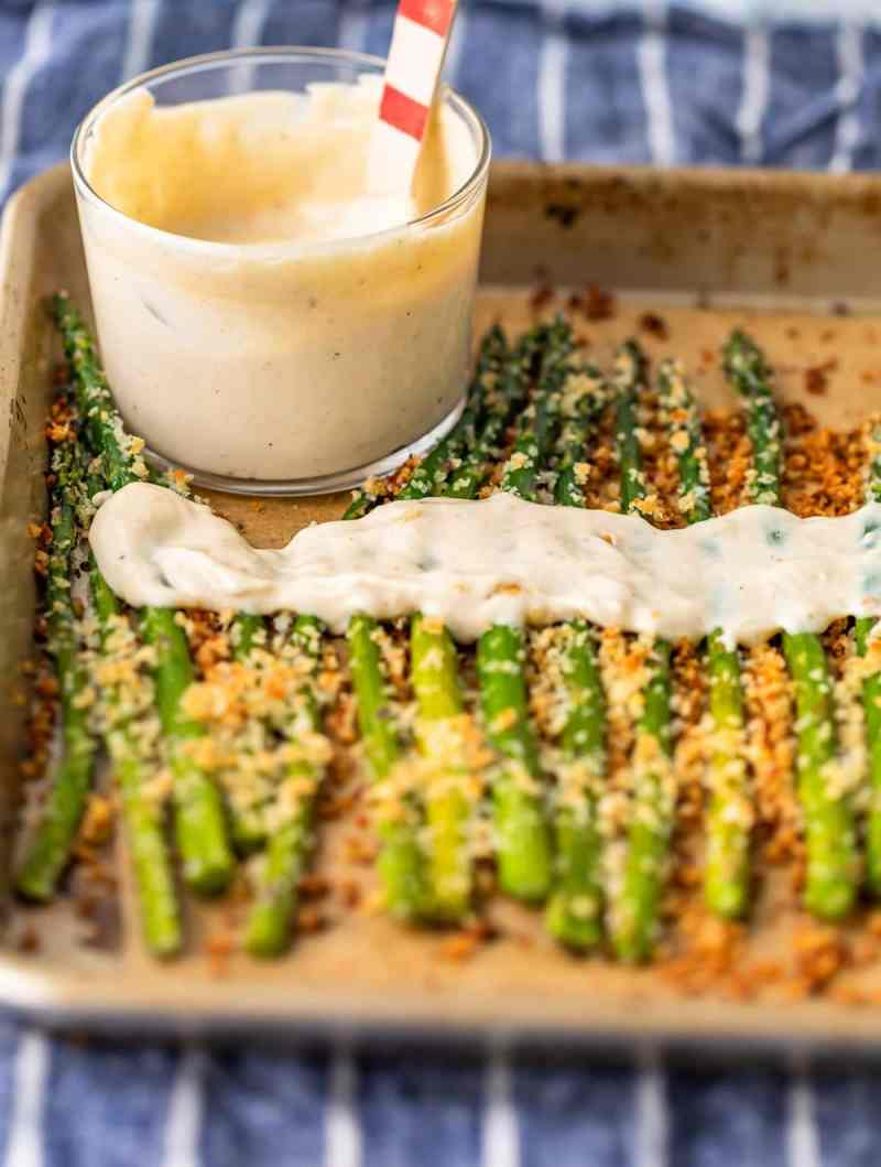 a bowl of aioli on a baking sheet with asparagus