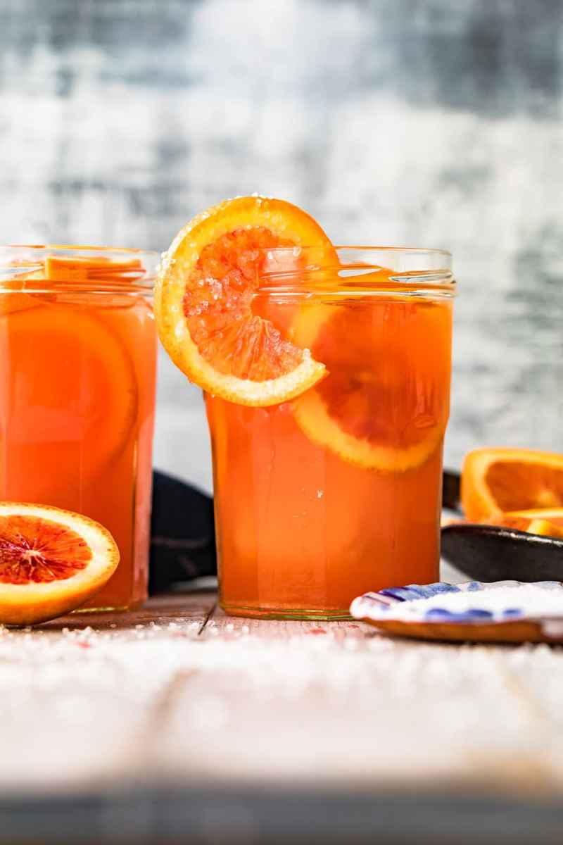 Two blood orange paloma cocktails served in mason jars